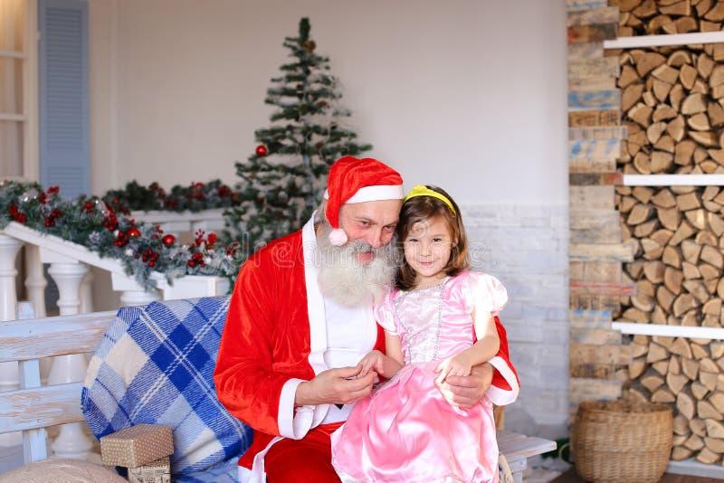 Εύθυμος Άγιος Βασίλης που μιλά στο μικρό κορίτσι στοκ φωτογραφίες