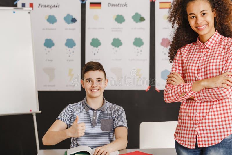 Εύθυμος δάσκαλος και ευτυχής σπουδαστής με τον αντίχειρα επάνω στοκ φωτογραφίες