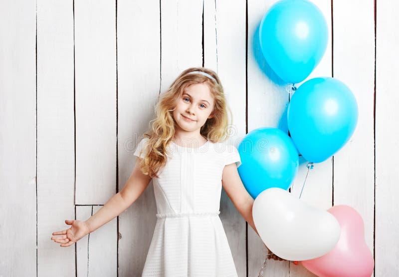 Εύθυμος λίγο ξανθό κορίτσι με τα μπαλόνια στο άσπρο ξύλινο backgrou στοκ φωτογραφία με δικαίωμα ελεύθερης χρήσης