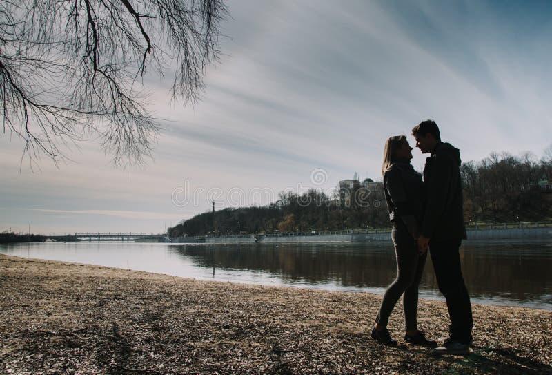 Εύθυμος αγαπώντας ο ένας τον άλλον φιλιά ζευγών Ο περίπατος στην όχθη ποταμού και αγκαλιάζει στοκ εικόνες με δικαίωμα ελεύθερης χρήσης
