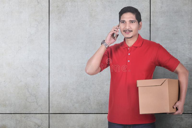 Εύθυμος ασιατικός αρσενικός αγγελιαφόρος που χρησιμοποιεί το κινητό τηλέφωνο κρατώντας το θόριο στοκ φωτογραφία