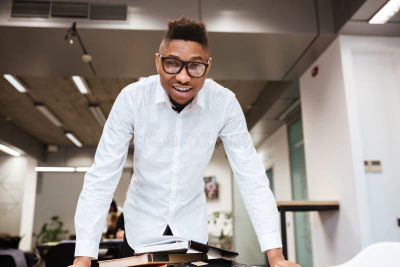 Εύθυμος αφρικανικός σπουδαστής στο υλικό εκπαίδευσης εκμάθησης βιβλιοθηκών στοκ φωτογραφία με δικαίωμα ελεύθερης χρήσης