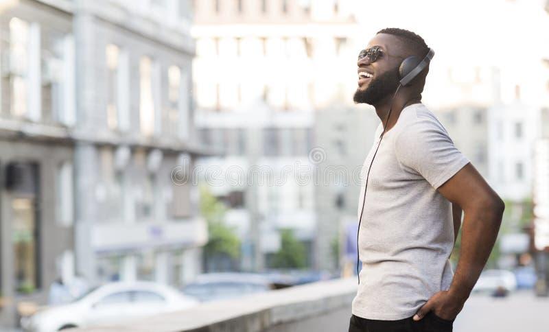 Εύθυμος αφρικανικός τύπος στην απόλαυση ακουστικών που ακούει τη μουσική στοκ εικόνες
