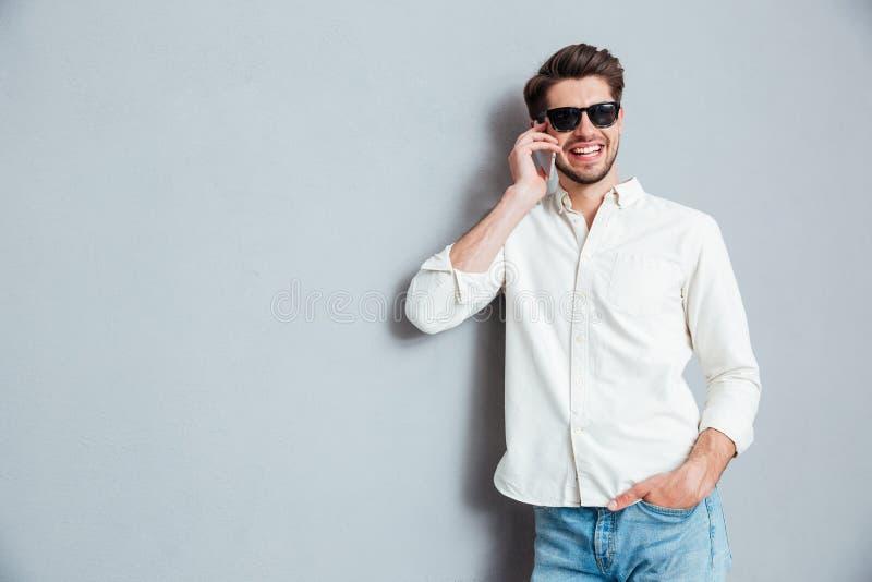 Εύθυμος βέβαιος νεαρός άνδρας στα γυαλιά ηλίου που μιλούν στο τηλέφωνο κυττάρων στοκ εικόνες