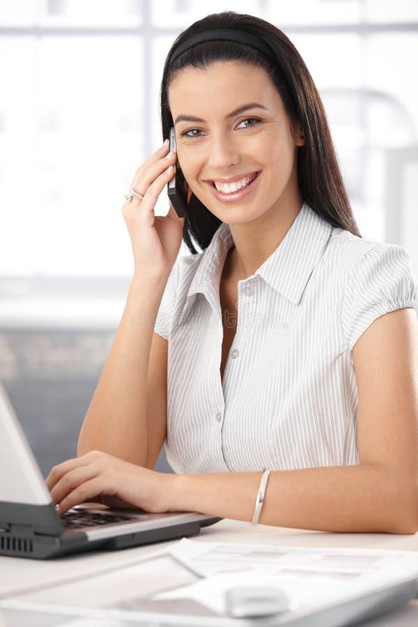 Εύθυμος βοηθός γραφείων στην κλήση στοκ εικόνα