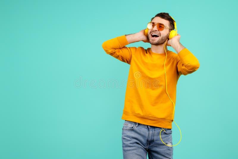 Εύθυμος γενειοφόρος νεαρός άνδρας που φορά τα κίτρινα γυαλιά ηλίου που ακούνε τη μουσική με τα κίτρινα ακουστικά στο κυανό υπόβαθ στοκ εικόνα με δικαίωμα ελεύθερης χρήσης