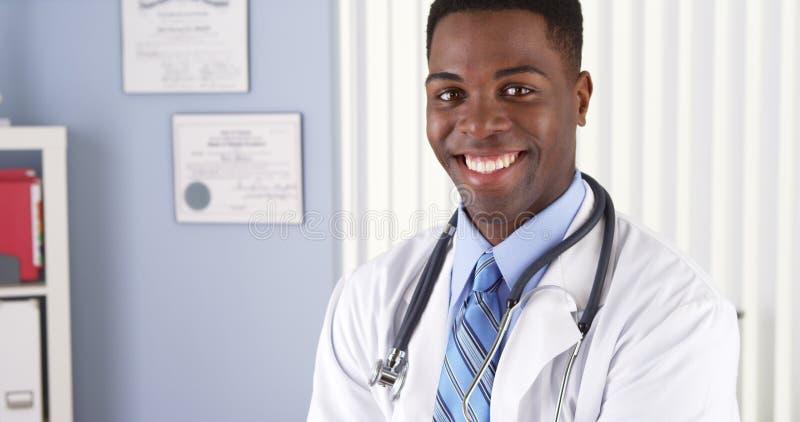 Εύθυμος γιατρός αφροαμερικάνων που στέκεται στο γραφείο του στοκ φωτογραφία