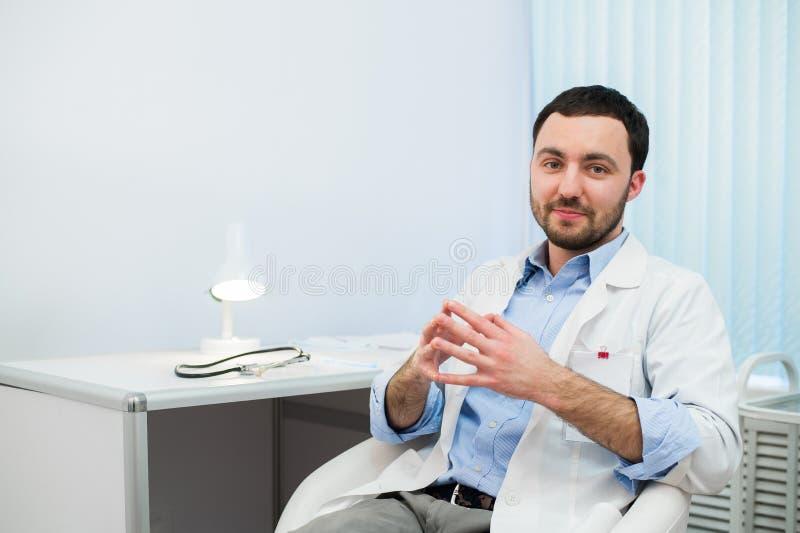 Εύθυμος γιατρός που μιλά και που εξετάζει τη κάμερα Παθολόγος στη συνομιλία με τον ασθενή καθμένος στο νοσοκομείο στοκ φωτογραφίες