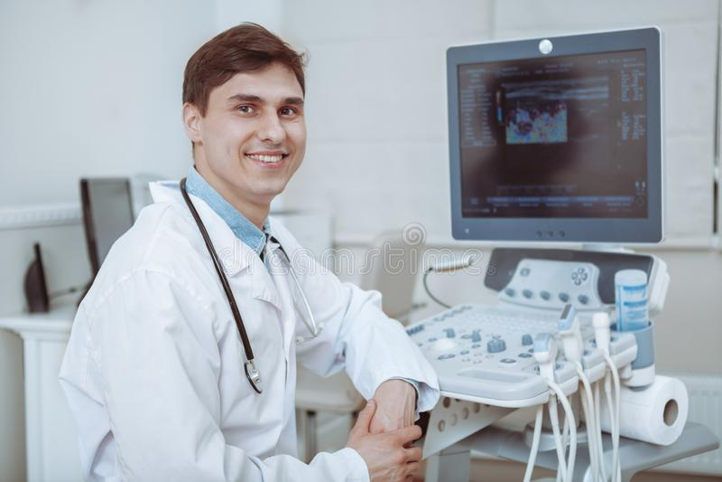 Εύθυμος γιατρός που χρησιμοποιεί τον ανιχνευτή υπερήχου στην εργασία στοκ φωτογραφίες με δικαίωμα ελεύθερης χρήσης