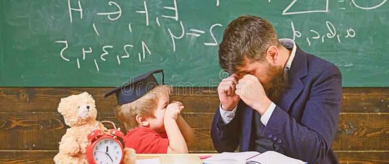 Εύθυμος εγκιβωτισμός παιδιών, κτυπώντας μπαμπάς Εύθυμη έννοια παιδιών Δάσκαλος και μαθητής στο mortarboard, πίνακας κιμωλίας στο  στοκ εικόνες