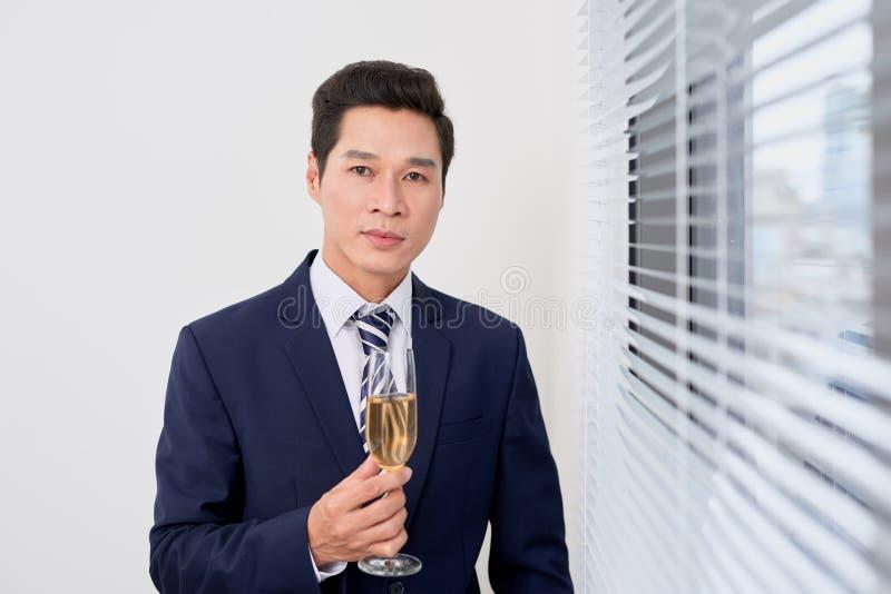 Εύθυμος επιχειρηματίας που δίνει τη φρυγανιά με τη σαμπάνια στοκ εικόνα