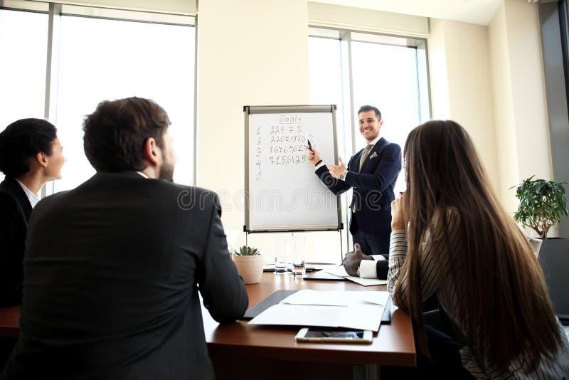 Εύθυμος επιχειρηματίας που συζητά το νέο επιχειρησιακό πρόγραμμα με τα μέλη της ομάδας του στοκ εικόνα