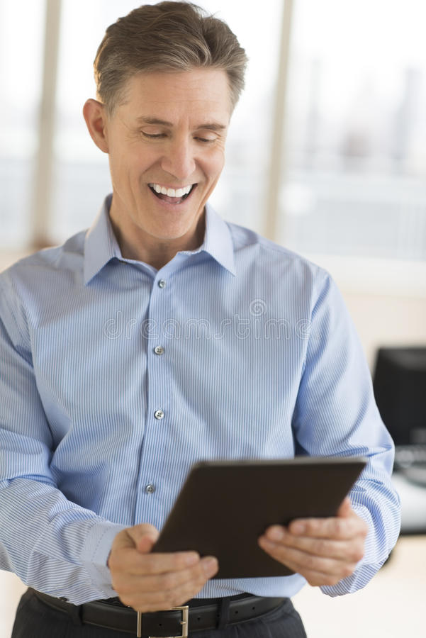 Εύθυμος επιχειρηματίας που χρησιμοποιεί την ψηφιακή ταμπλέτα στοκ εικόνες