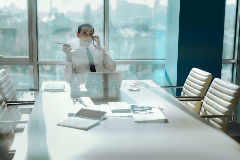 Εύθυμος εργαζόμενος γραφείων που κουβεντιάζει στο τηλέφωνο κατά τη διάρκεια του σπασίματος στοκ φωτογραφία