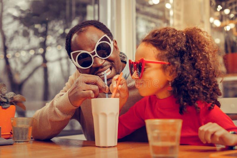 Εύθυμος ευτυχής πατέρας που φορά τα φωτεινά γυαλιά ηλίου και που πίνει milkshake στοκ εικόνα με δικαίωμα ελεύθερης χρήσης