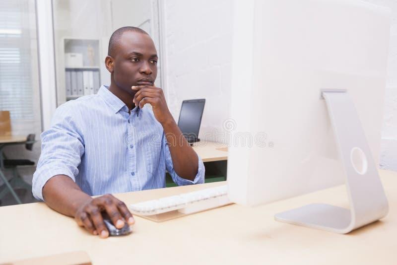 Εύθυμος δημιουργικός επιχειρηματίας που εργάζεται στον υπολογιστή στοκ εικόνα