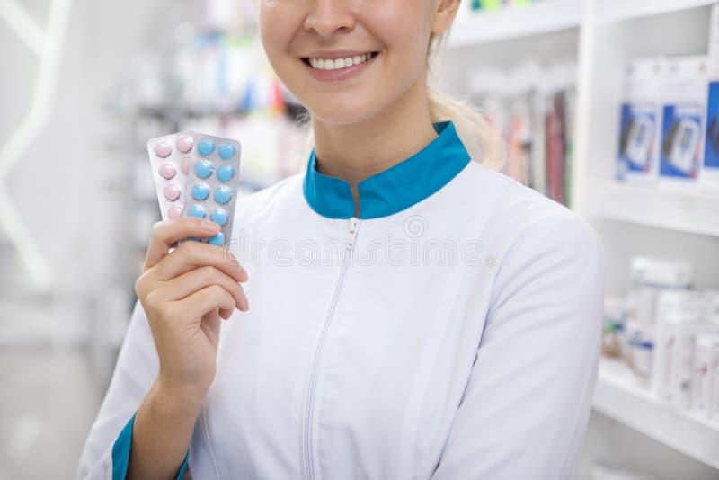 Εύθυμος θηλυκός φαρμακοποιός που εργάζεται στο φαρμακείο στοκ εικόνες με δικαίωμα ελεύθερης χρήσης