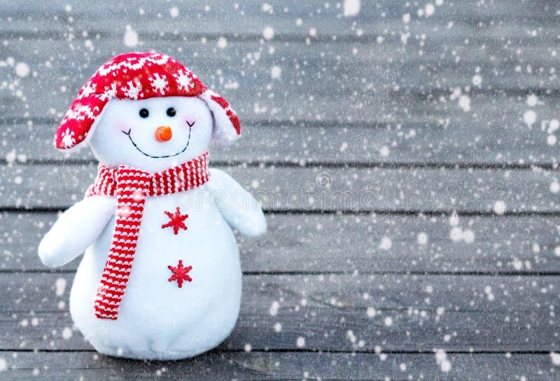 Εύθυμος και αστείος χιονάνθρωπος σε ένα κόκκινο καπέλο και κόκκινο μαντίλι σε ένα γκρίζο ξύλινο υπόβαθρο Μειωμένη σύσταση χιονιού στοκ εικόνες με δικαίωμα ελεύθερης χρήσης