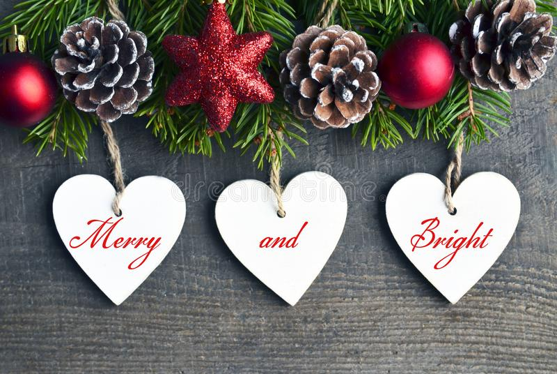 Εύθυμος και φωτεινός Διακόσμηση Χριστουγέννων με το δέντρο έλατου, τους κώνους πεύκων, και τις άσπρες ξύλινες καρδιές στο παλαιό  στοκ φωτογραφία με δικαίωμα ελεύθερης χρήσης