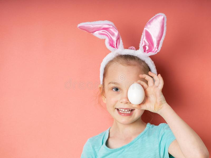 Εύθυμος λίγο κορίτσι παιδιών με τα αυτιά λαγουδάκι με το άσπρο αυγό Πάσχας στο ρόδινο υπόβαθρο στοκ φωτογραφία με δικαίωμα ελεύθερης χρήσης