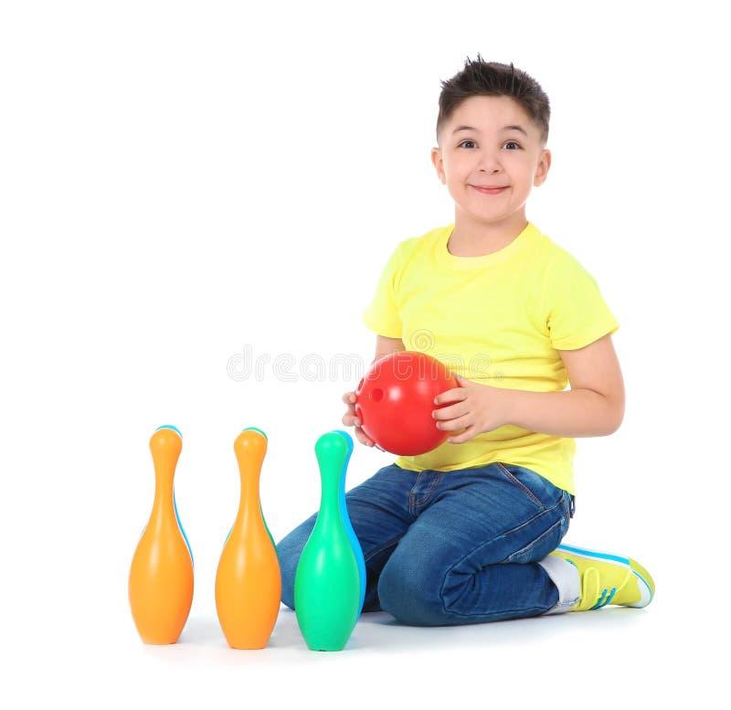 Εύθυμος λίγο παιδί με το πλαστικό σύνολο μπόουλινγκ στοκ εικόνες