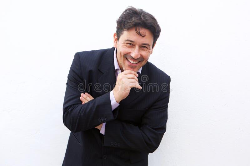 Εύθυμος μέσος ηλικίας επιχειρηματίας που στέκεται στο άσπρο κλίμα στοκ φωτογραφία