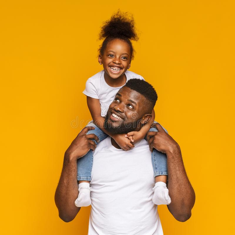 Εύθυμος μαύρος που οδηγά τη χαριτωμένη μικρή κόρη του στους ώμους στοκ φωτογραφίες