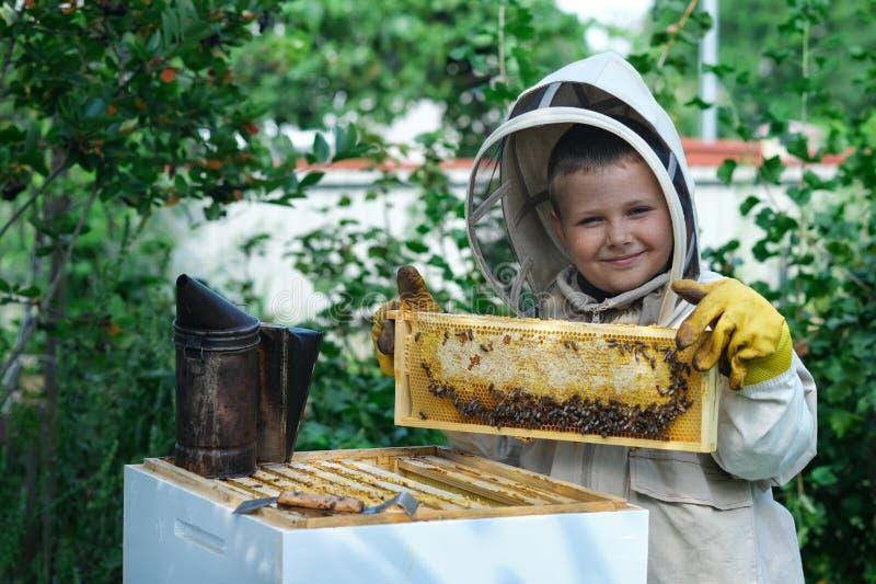 Εύθυμος μελισσοκόμος αγοριών στο προστατευτικό κοστούμι κοντά στην κυψέλη Κηρήθρα με το μέλι Έννοια οργανικής τροφής Το πιό χρήσι στοκ εικόνα με δικαίωμα ελεύθερης χρήσης