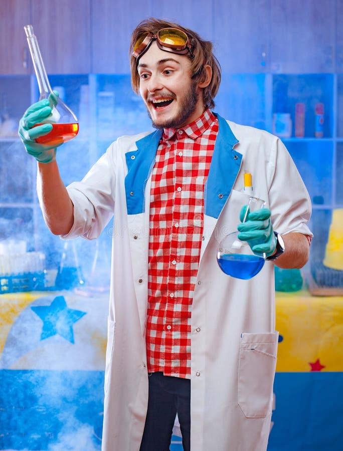 Εύθυμος νέος επιστήμονας με τις φιάλες στοκ εικόνες