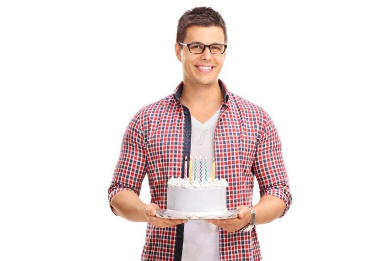 Εύθυμος νέος τύπος που κρατά ένα κέικ γενεθλίων στοκ εικόνα με δικαίωμα ελεύθερης χρήσης
