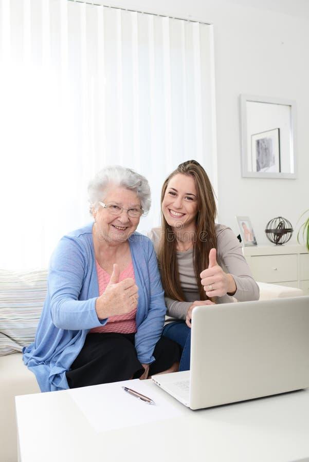 Εύθυμος νέος υπολογιστής διδασκαλίας γυναικών σε μια ηλικιωμένη ανώτερη γυναίκα στο σπίτι στοκ φωτογραφία με δικαίωμα ελεύθερης χρήσης