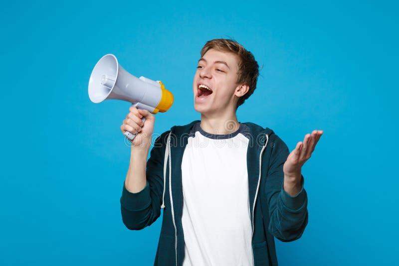 Εύθυμος νεαρός άνδρας στα περιστασιακά ενδύματα που κοιτάζει κατά μέρος, κραυγάζοντας megaphone, χέρια διάδοσης που απομονώνονται στοκ εικόνα