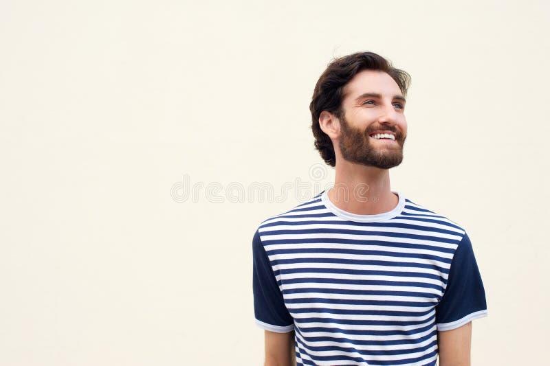 Εύθυμος νεαρός άνδρας με τη γενειάδα που χαμογελά στο άσπρο υπόβαθρο στοκ φωτογραφία με δικαίωμα ελεύθερης χρήσης