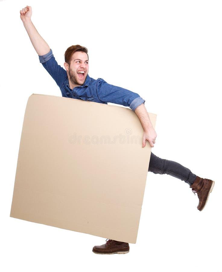 Εύθυμος νεαρός άνδρας που κρατά την κενή αφίσα στοκ φωτογραφία με δικαίωμα ελεύθερης χρήσης