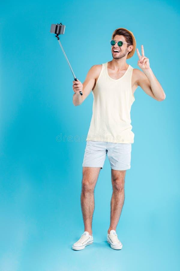 Εύθυμος νεαρός άνδρας που παίρνει selfie με το smartphone και monopod στοκ εικόνα