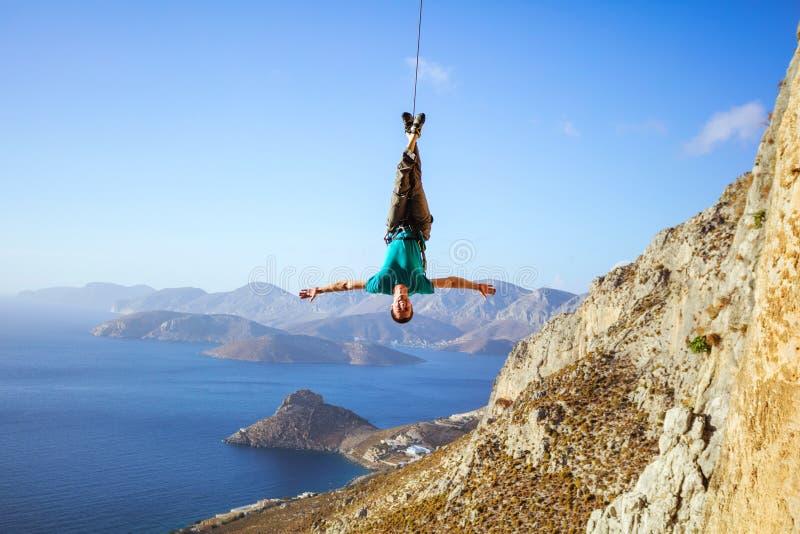 Εύθυμος ορειβάτης βράχου που ταλαντεύεται στην άνω πλευρά σχοινιών - κάτω στοκ εικόνες με δικαίωμα ελεύθερης χρήσης
