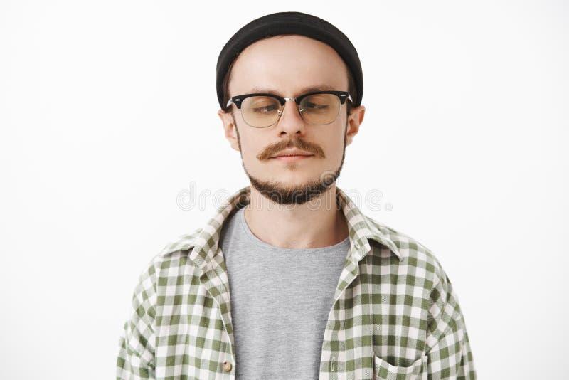 Εύθυμος παιδαριώδης όμορφος νέος τύπος με το moustache και τη γενειάδα στα γυαλιά και μαύρο καθιερώνον τη μόδα beanie που εξετάζε στοκ εικόνες με δικαίωμα ελεύθερης χρήσης