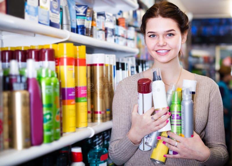 Εύθυμος πελάτης γυναικών που αποφασίζει σχετικά με τα προϊόντα προσοχής τρίχας στο κατάστημα στοκ εικόνες