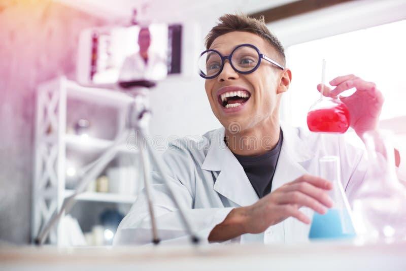 Εύθυμος σπουδαστής που φορά τα γυαλιά που αισθάνονται το πολύ συναισθηματικό κάνοντας πείραμα στοκ φωτογραφία με δικαίωμα ελεύθερης χρήσης