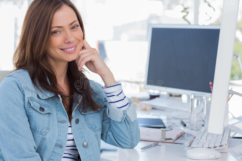Εύθυμος σχεδιαστής που χαμογελά στο δημιουργικό γραφείο στοκ εικόνα με δικαίωμα ελεύθερης χρήσης