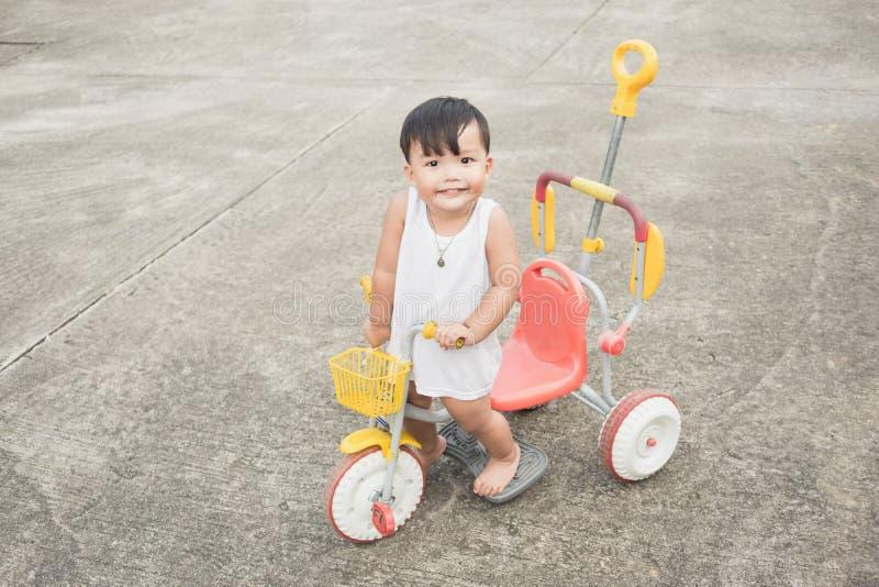 Εύθυμος της στάσης μωρών στο ποδήλατο και να φανεί παιδιών ` s κάμερα στο υπόβαθρο συγκεκριμένων δρόμων στοκ εικόνες