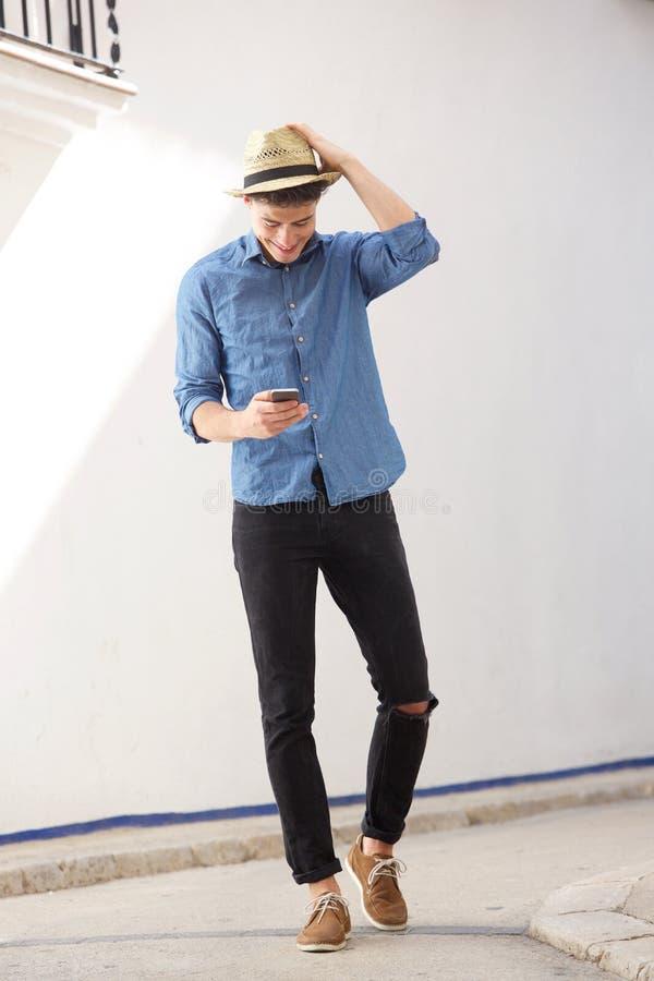 Εύθυμος τύπος που περπατά και που διαβάζει το μήνυμα κειμένου στο τηλέφωνο κυττάρων στοκ φωτογραφία με δικαίωμα ελεύθερης χρήσης