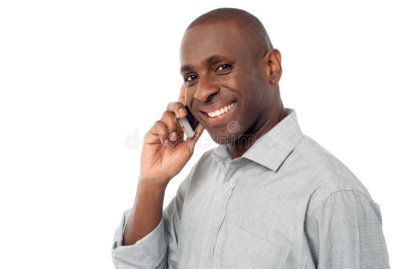 Εύθυμος τύπος που χρησιμοποιεί το κινητό τηλέφωνό του στοκ φωτογραφίες