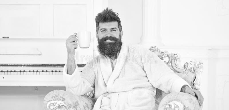 Εύθυμος τύπος στο άσπρο μπουρνούζι που απολαμβάνει τον καφέ πρωινού Γενειοφόρος συνεδρίαση ατόμων στην όμορφη παλαιά πολυθρόνα εν στοκ φωτογραφίες με δικαίωμα ελεύθερης χρήσης