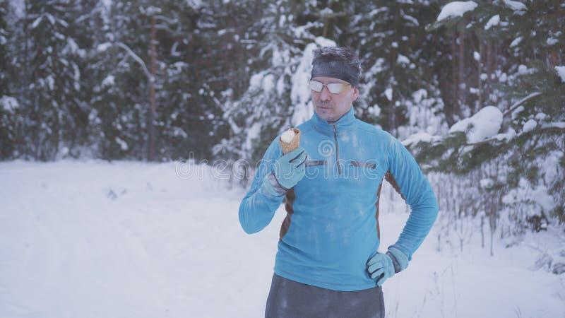 Εύθυμος υγιής άνδρας, υπάρχει παγωτό το χειμώνα, ισχυρή ασυλία στοκ εικόνες με δικαίωμα ελεύθερης χρήσης
