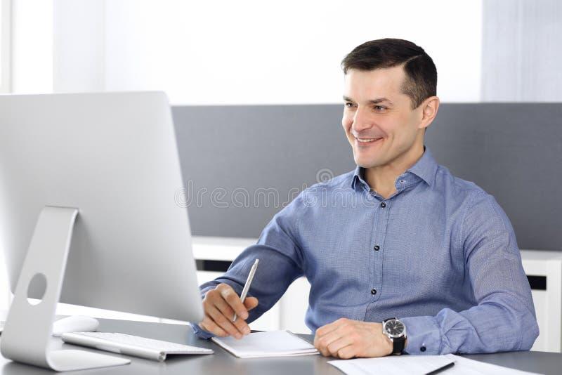 Εύθυμος χαμογελώντας επιχειρηματίας που εργάζεται με τον υπολογιστή στο σύγχρονο γραφείο Headshot του αρσενικού επιχειρηματία ή τ στοκ φωτογραφία με δικαίωμα ελεύθερης χρήσης