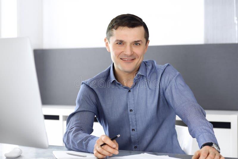 Εύθυμος χαμογελώντας επιχειρηματίας που εργάζεται με τον υπολογιστή στο σύγχρονο γραφείο Headshot του αρσενικού επιχειρηματία ή τ στοκ φωτογραφία