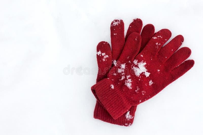 Εύθυμος χειμώνας Γάντια που βρίσκονται στο υπόβαθρο χιονιού στοκ εικόνες