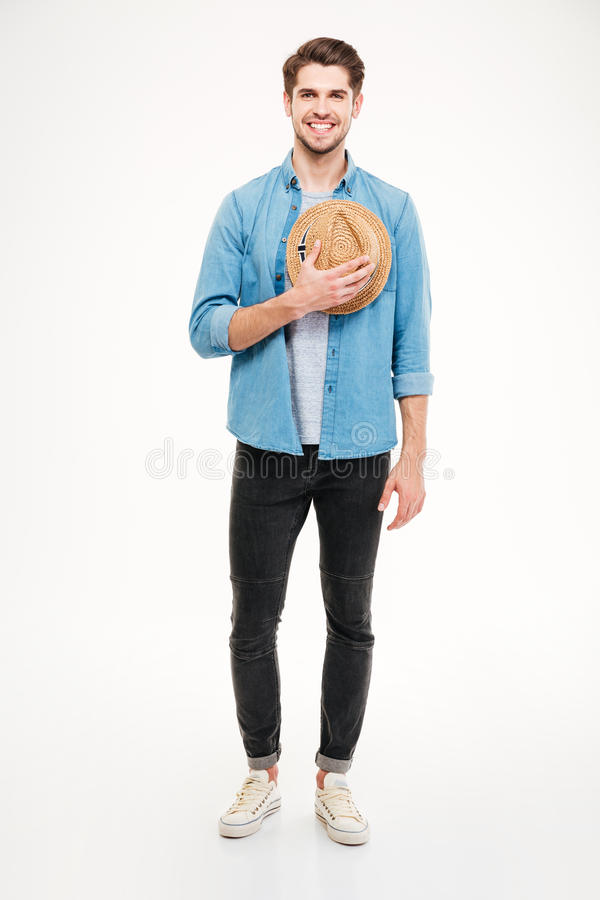 Εύθυμος όμορφος νεαρός άνδρας που στέκεται και που κρατά το καπέλο στοκ φωτογραφία