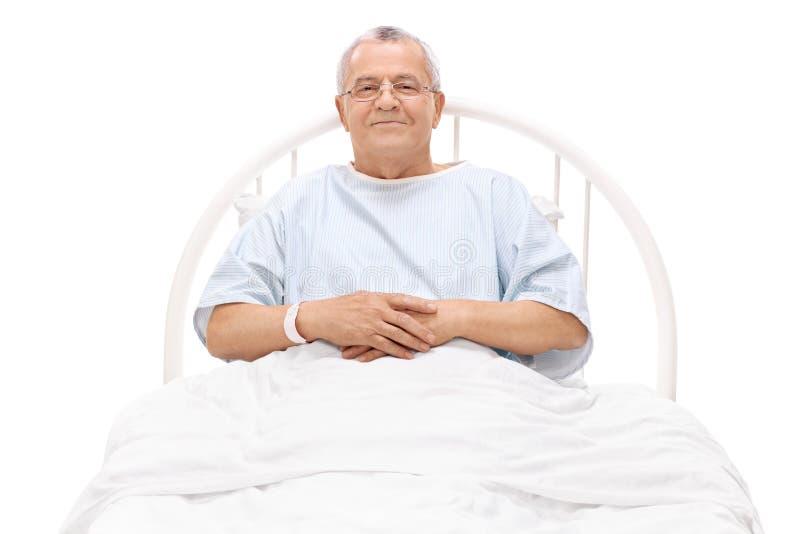 Εύθυμος ώριμος ασθενής που βρίσκεται σε ένα νοσοκομειακό κρεβάτι στοκ φωτογραφίες